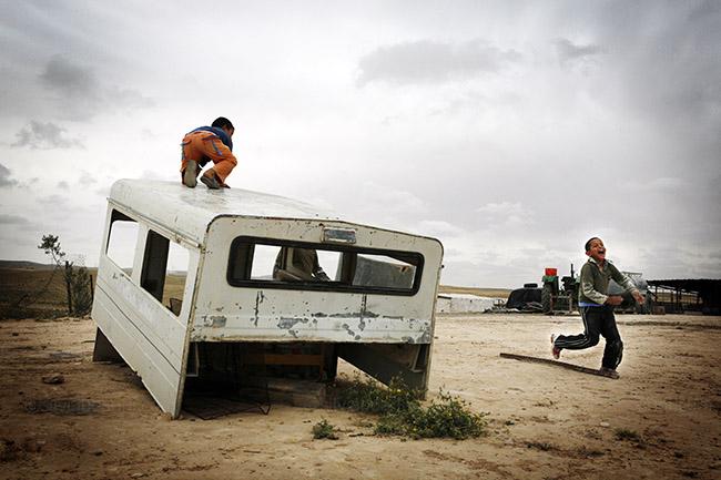 Children play on the skeleton of a car. El Arakeeb, Israel
