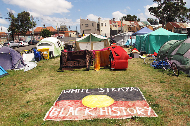 A flag in the middle of the camp reads 'white Australia has black history'. Redfern, Australia. 4/11/2014