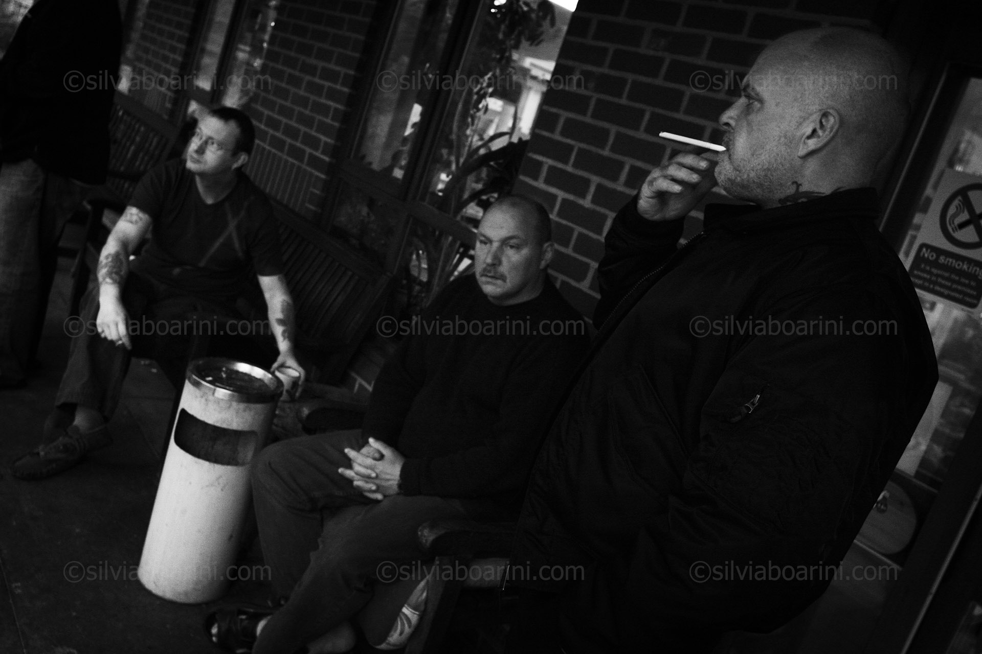Men gather outside for a cigarette and a chat, Leatherhead, UK