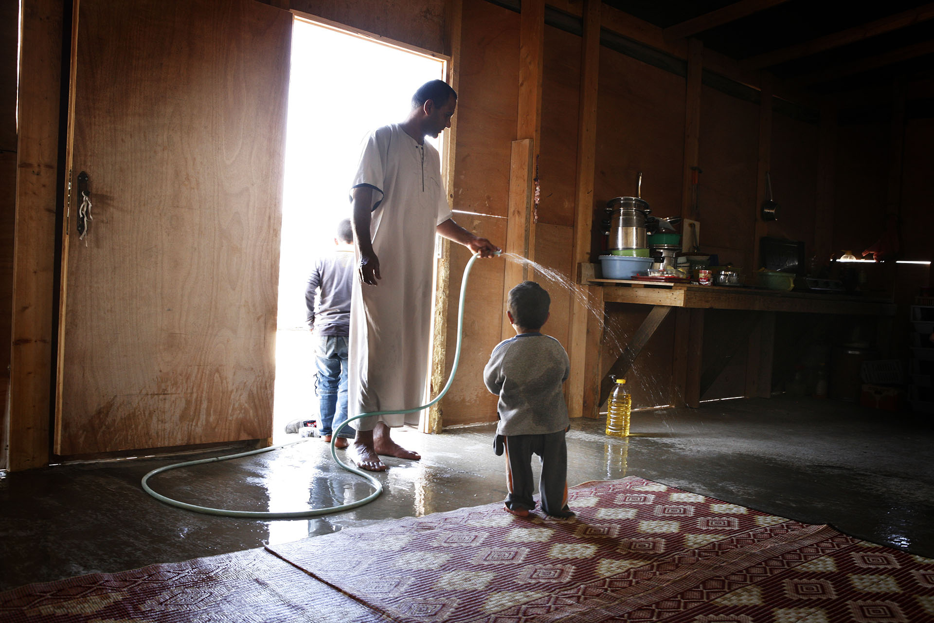 Azeez sprays water on the floor of the family home to cool it down. Al Araqib April 2009
