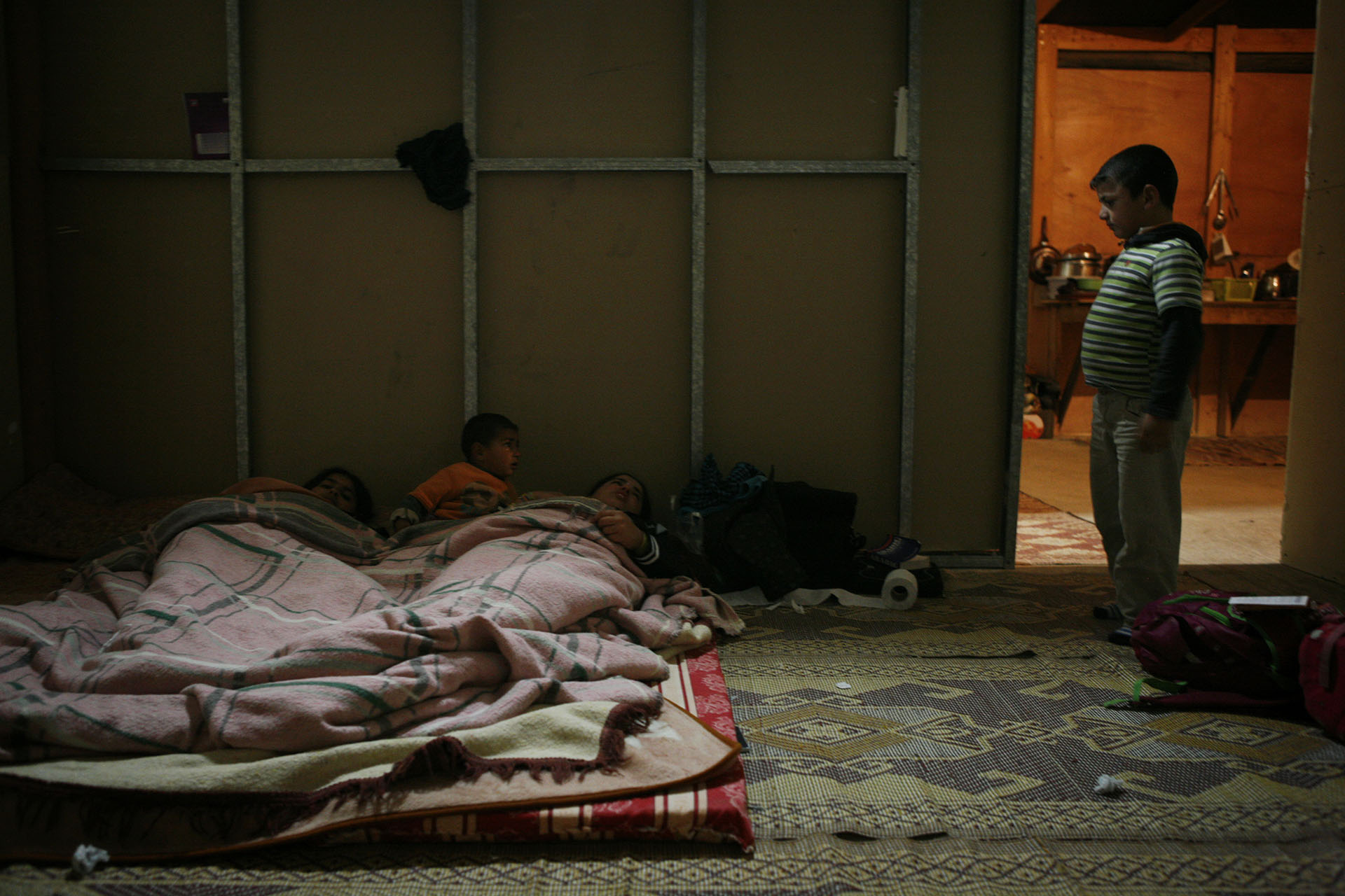 Said stands by the door as Hala, Fatima and Mohammed are in bed in their room. February 2010