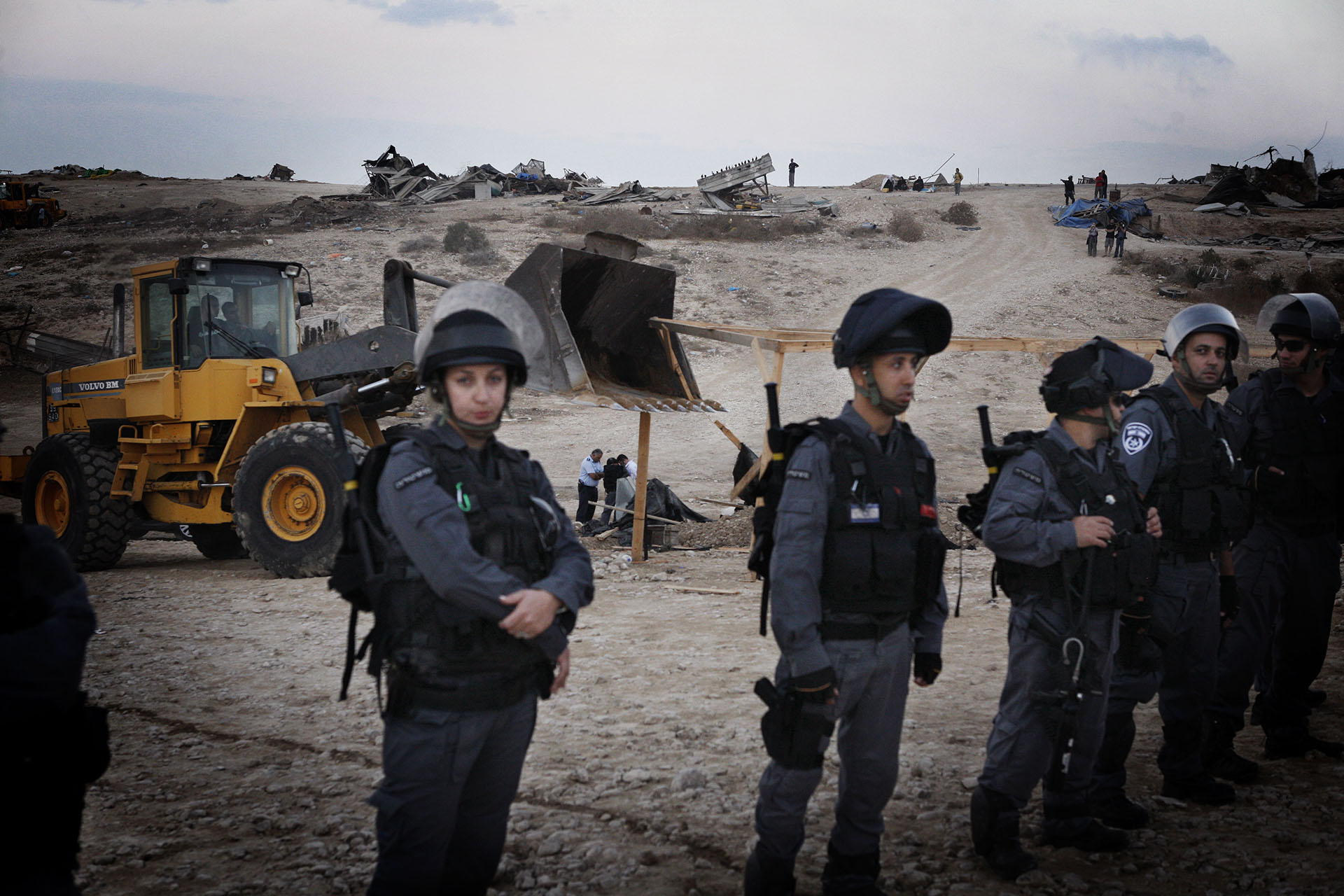Israeli police officers escort bulldozers. Some of the demolitions turned violent with rubber bullets and tear gas shot on the villagers, who reported a variety of injuries. September 2010