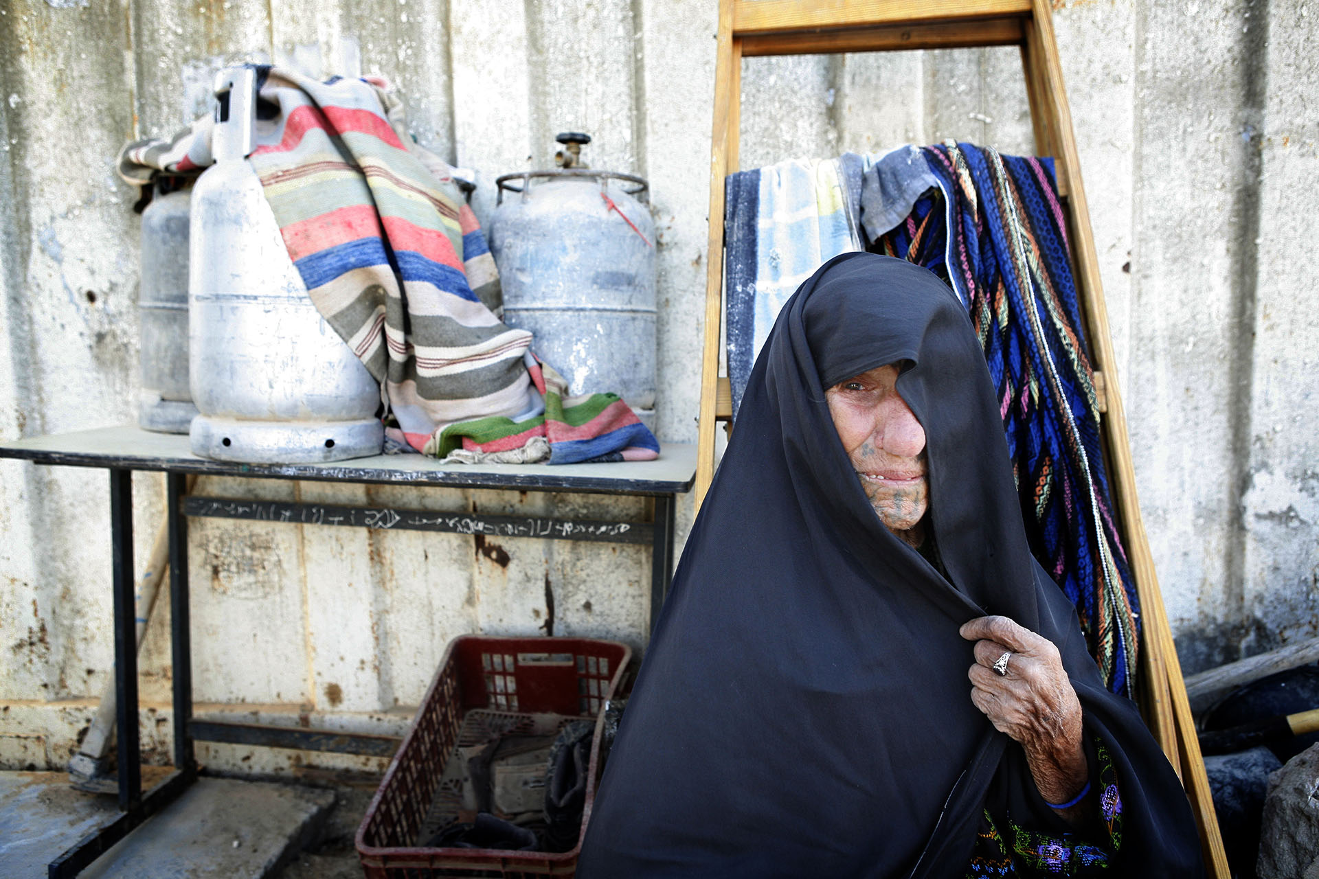 An elderly woman sits outside her family home. Al Araqib, July 2012