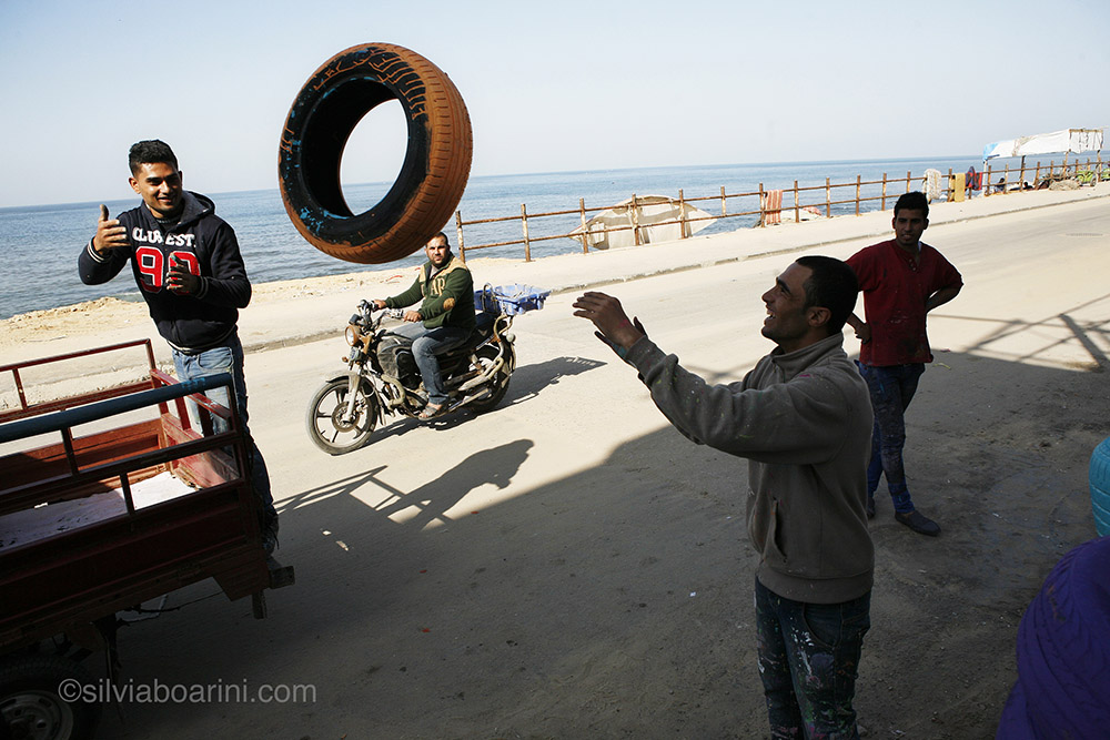 Project participants unload painted tyres from a tuk-tuk. Al Shati, Gaza