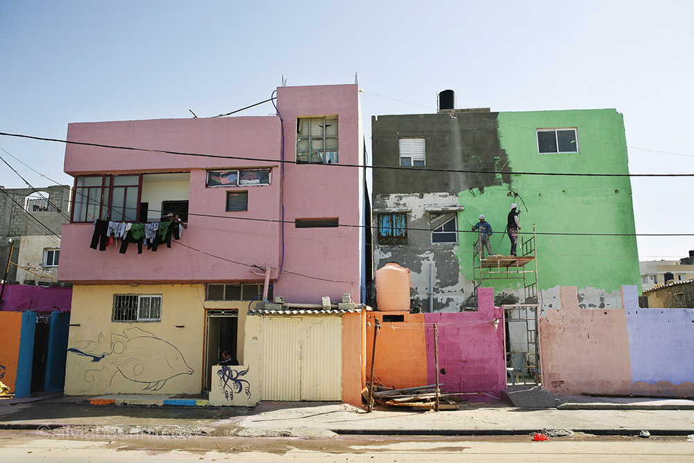 Men on a scaffolding paint the facade of one of the sea front homes. Al Shati, Gaza