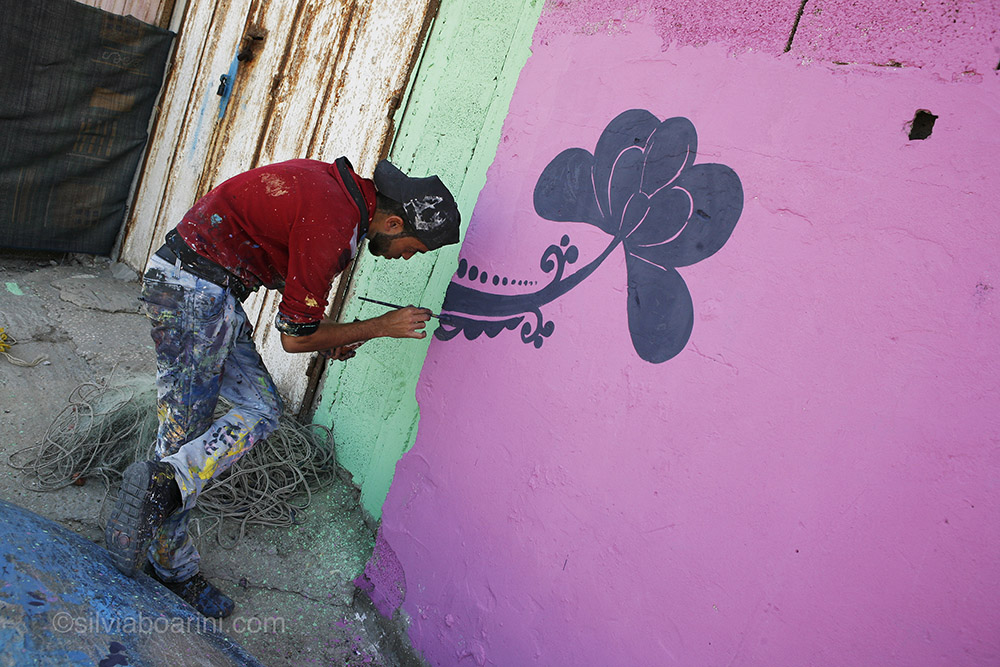 "Jehad Naiem Abaas, 25, an artist from Bet Lahia, takes part in the PADICO sponsored project to give Al Shati refugee camp a make-over. ""So kids can run around surrounded by colour,"" he said. Shati, Gaza"