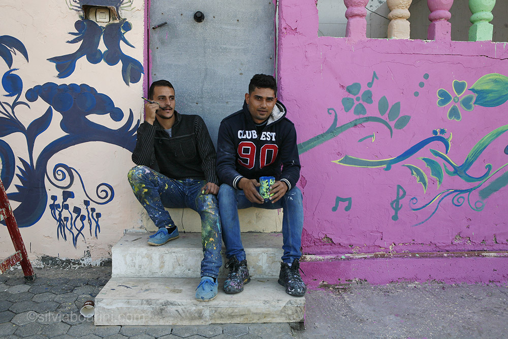 "Usama Abu Ambra, 27, left, sits on the steps of one the brightly painted homes in Al Shati refugee camp. The project was sponsored by the Palestinian share-holding company PADICO. Abu Amra didn't complete high school but works as a photographer and artist.  ""We are doing this so children can play in pleasant surrounding, to make Shati more beautiful"". Shati, Gaza"