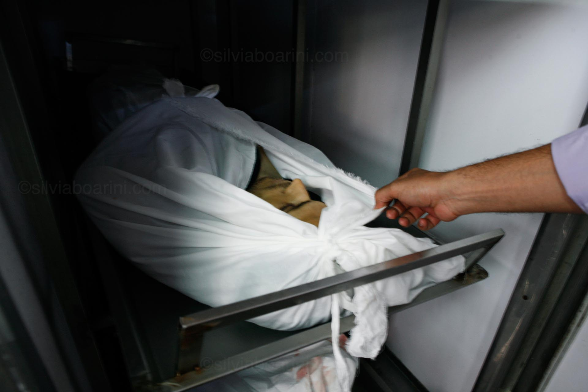 A doctor opens one of the morgue's units to show a young person brought in following shelling near Khan Younis. Khan Younis hospital, July 2014