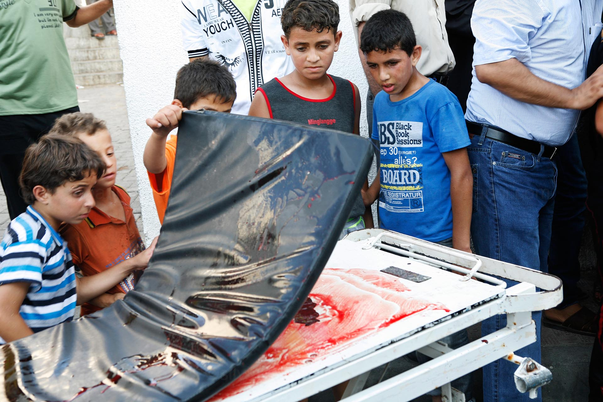With a mix of curiosity, fear and disgust, children hanging outside the Shifa hospital survey the blood on a trolley that brought in a body. Gaza, July 2014