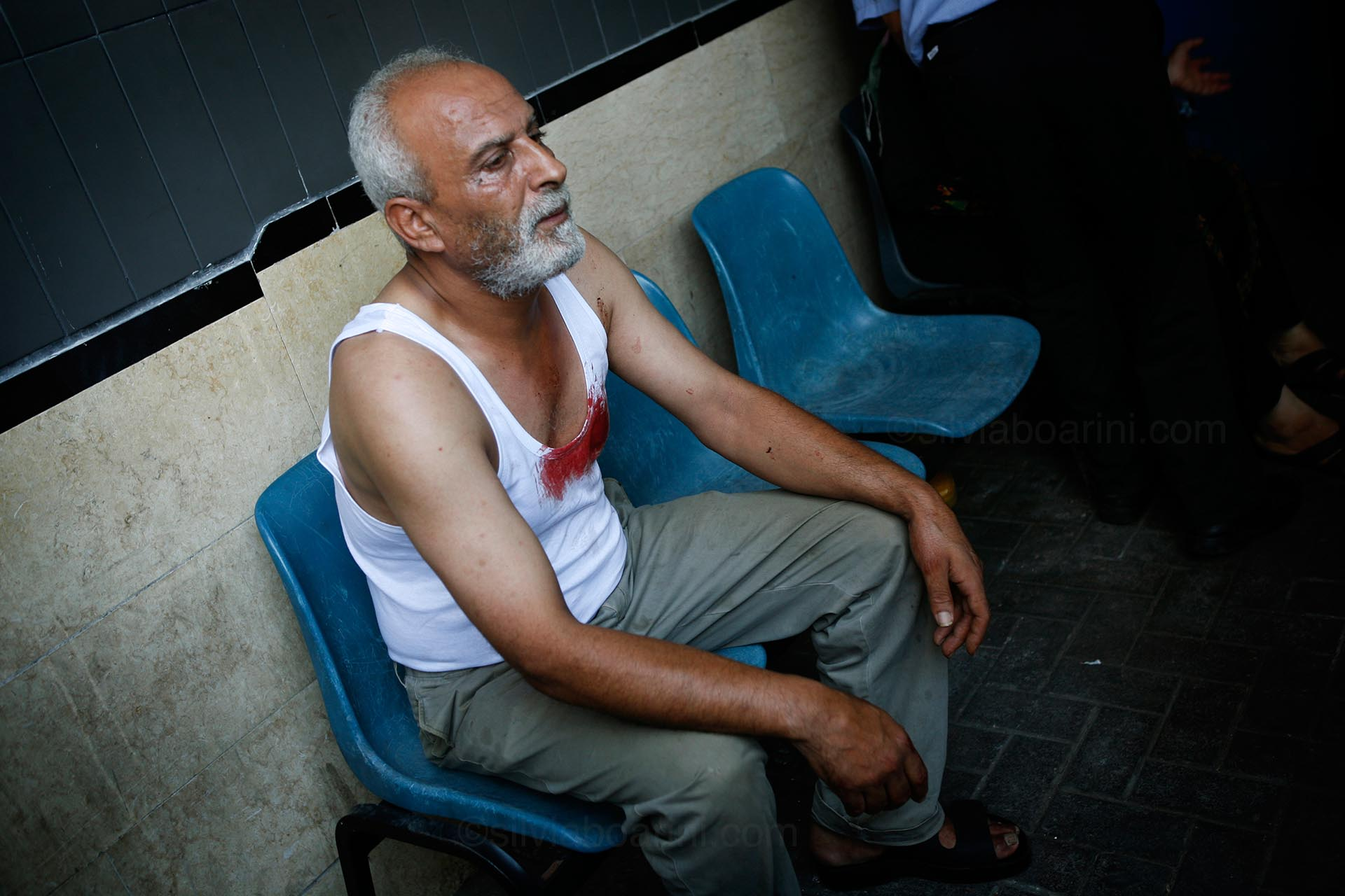 Relatives sit in shock outside Shifa hospital following an explosion at Shati camp, which killed 11 children. Amnesty International attributed the explosion to a misfired Palestinian rocket. Gaza 28 July 2014