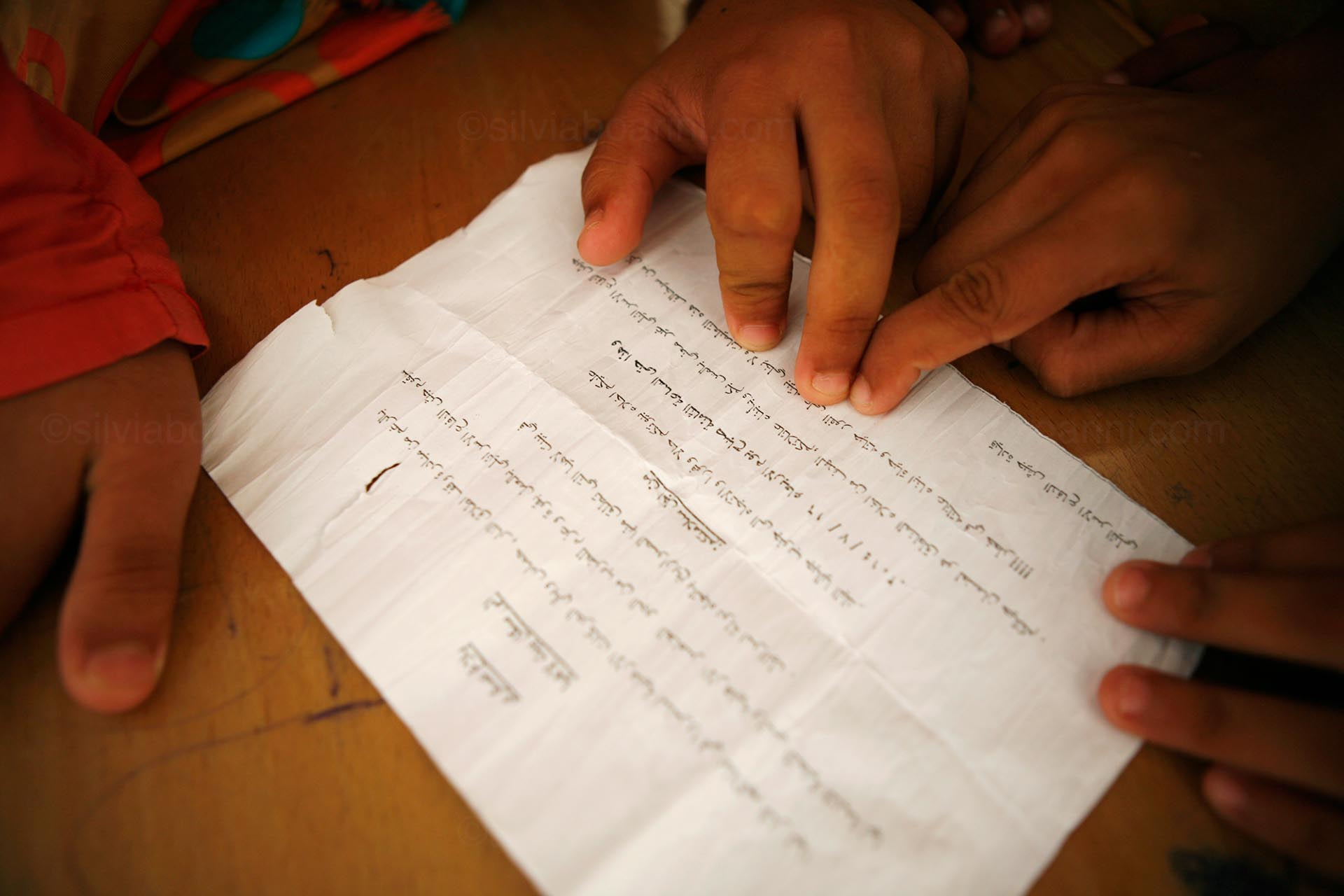 Children from the northern city of Beit Hanoun, now displaced to a UNRWA school in Gaza, read the leaflet that the Israeli air force dropped on their city. The leaflet warns civilians to evacuate the area before an imminent attack. Gaza, July 2014