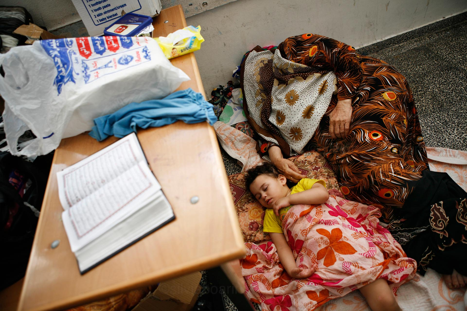 A grandmother sleeps next to her niece in a UNRWA school in Gaza. Gaza, July 2014