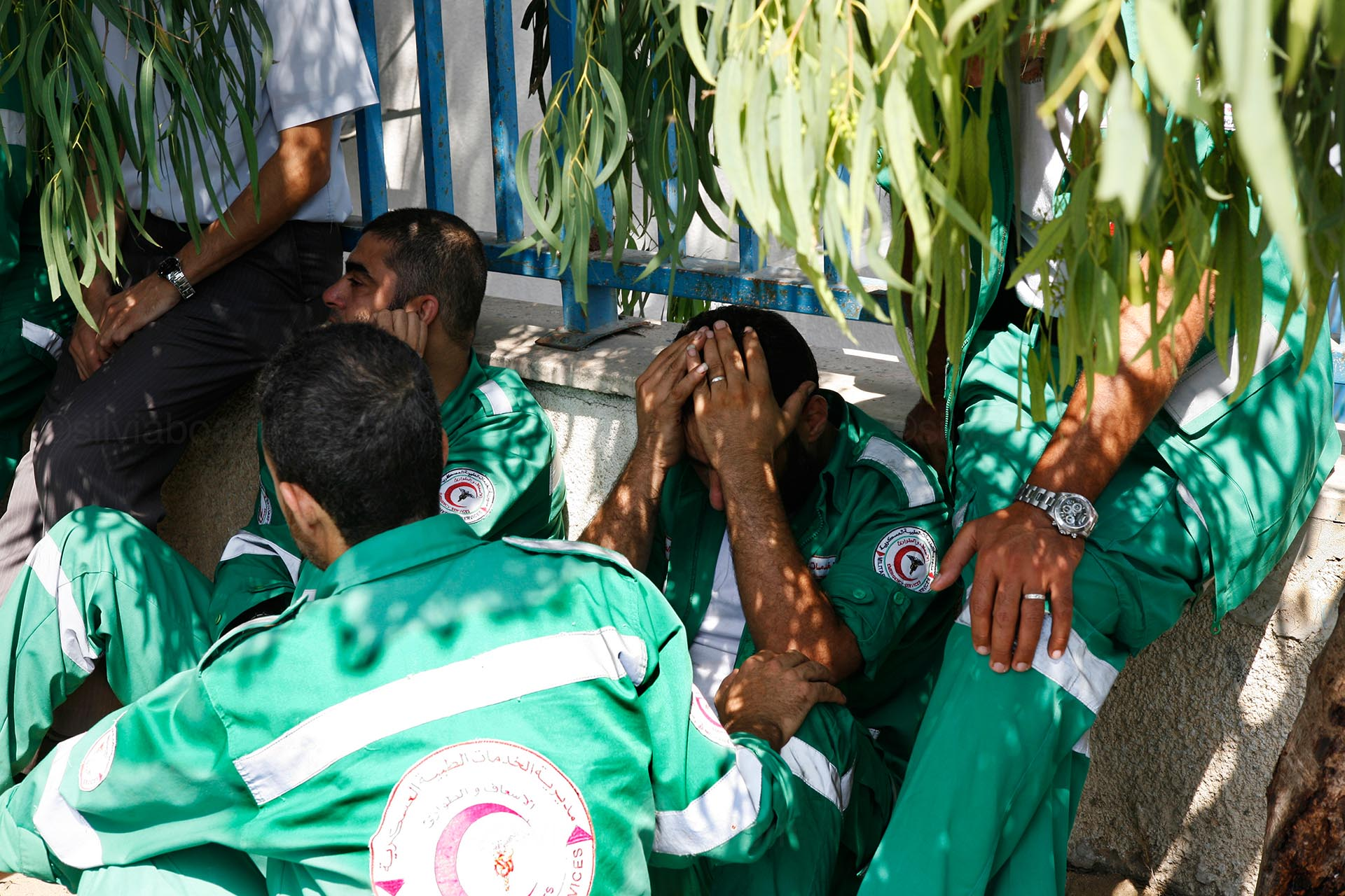 Paramedics sit in shock under a tree outside Shifa hospital after bringing in corpses from Shujayea. Gaza, 20 July 2014