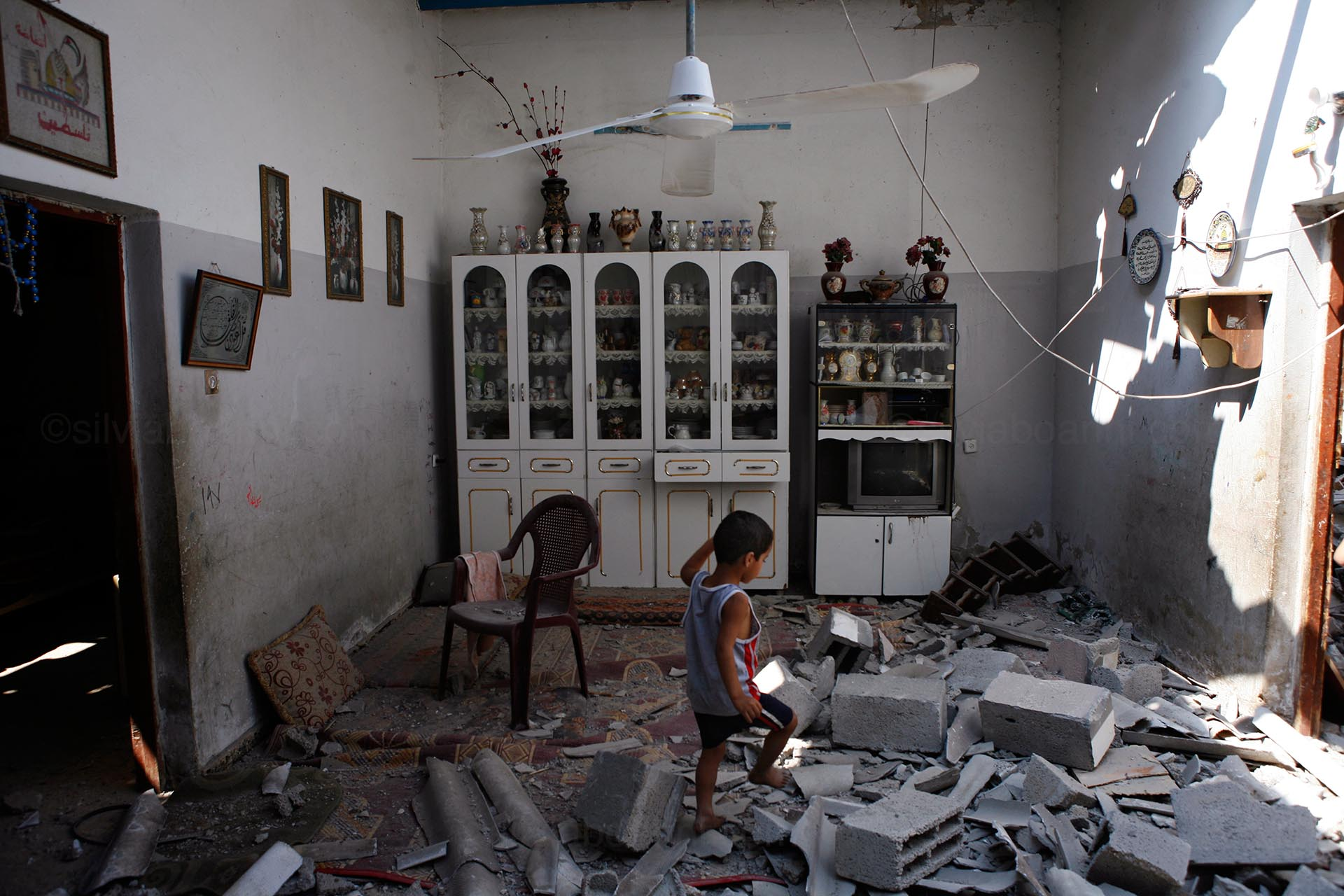 A child of the Abu Bakhr family walks in what used to be living room of his home, which was hit by an Israeli missile. Shati, Gaza, July 2014