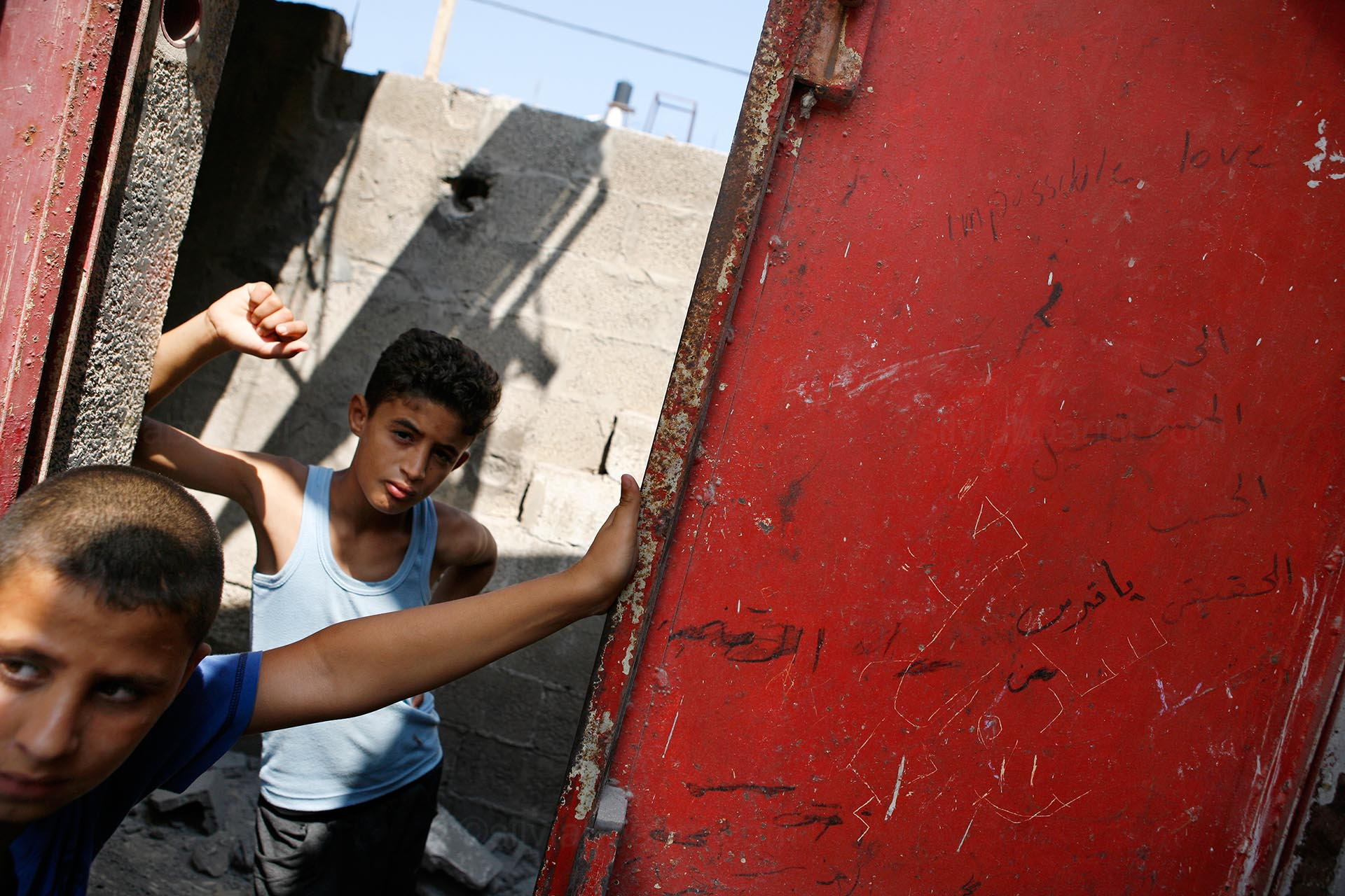 Children stand at the door of the Abu Bakhr home, which was bombed in the night. 'Impossible love' is written on the red metal door. Gaza, July 2014