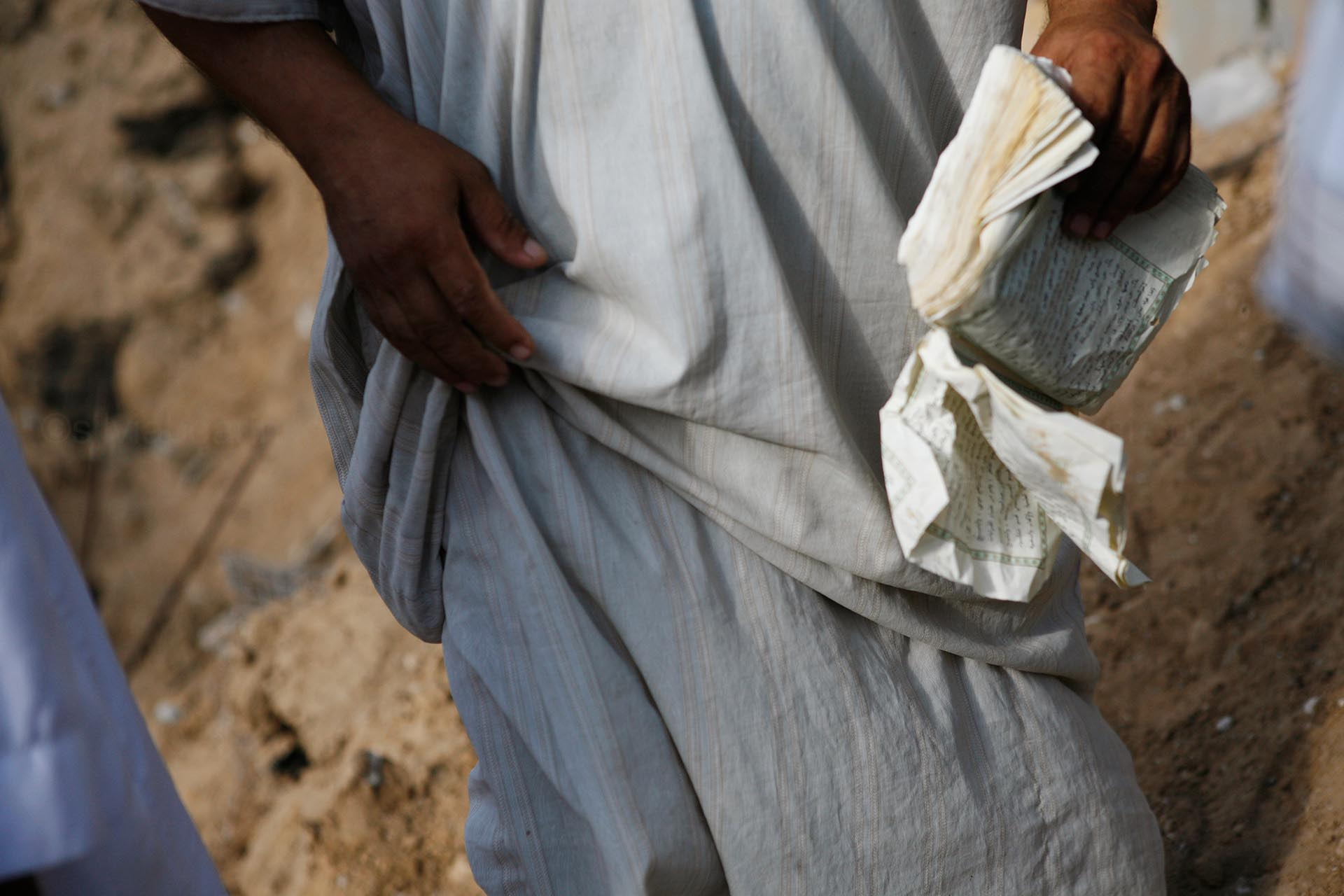 A man picks up pieces of the Holy Koran from the rubble. Abasan Al Kabira, July 2014