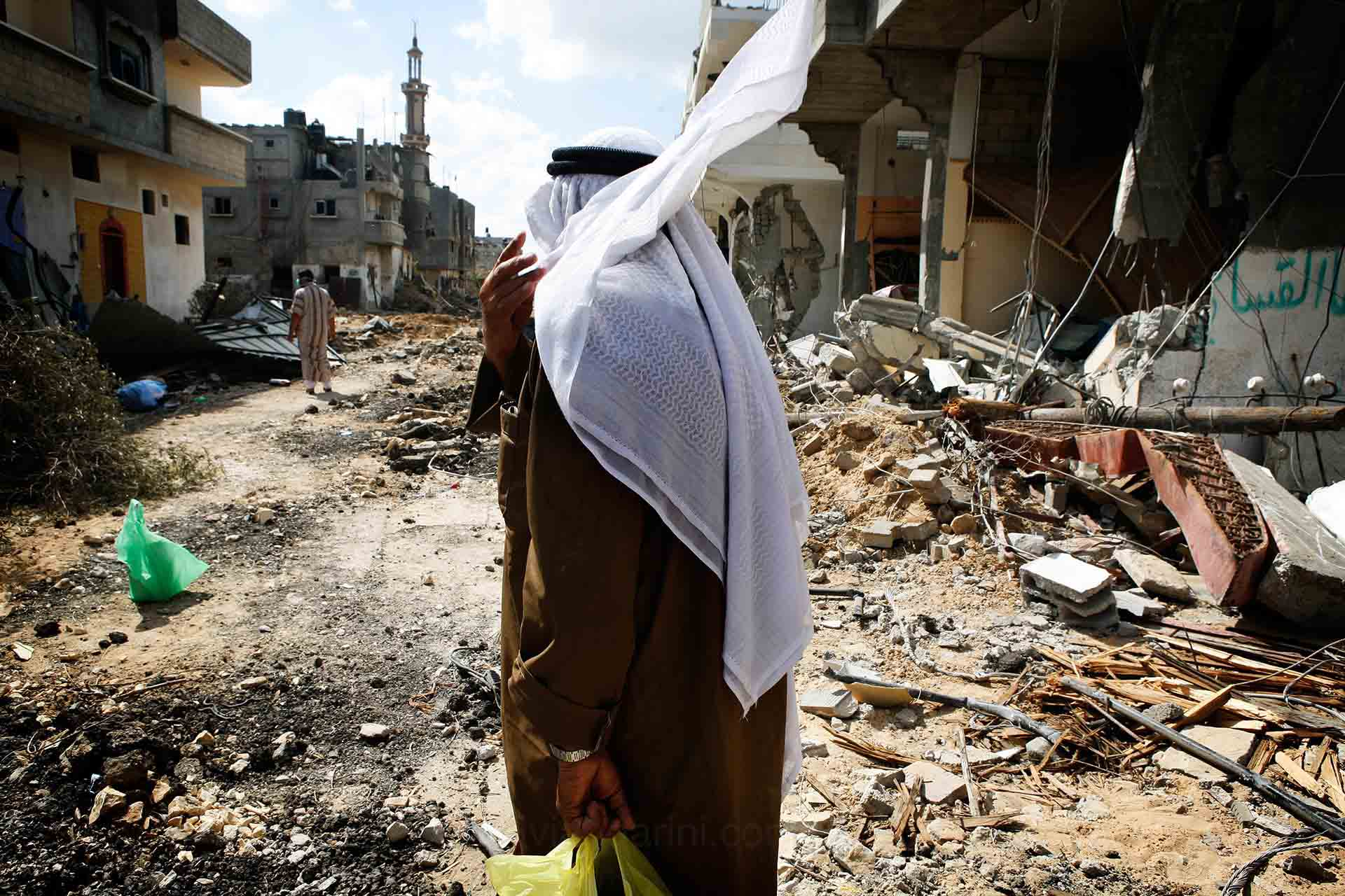 An elderly man walks through the rubble in Khouza. August 2014