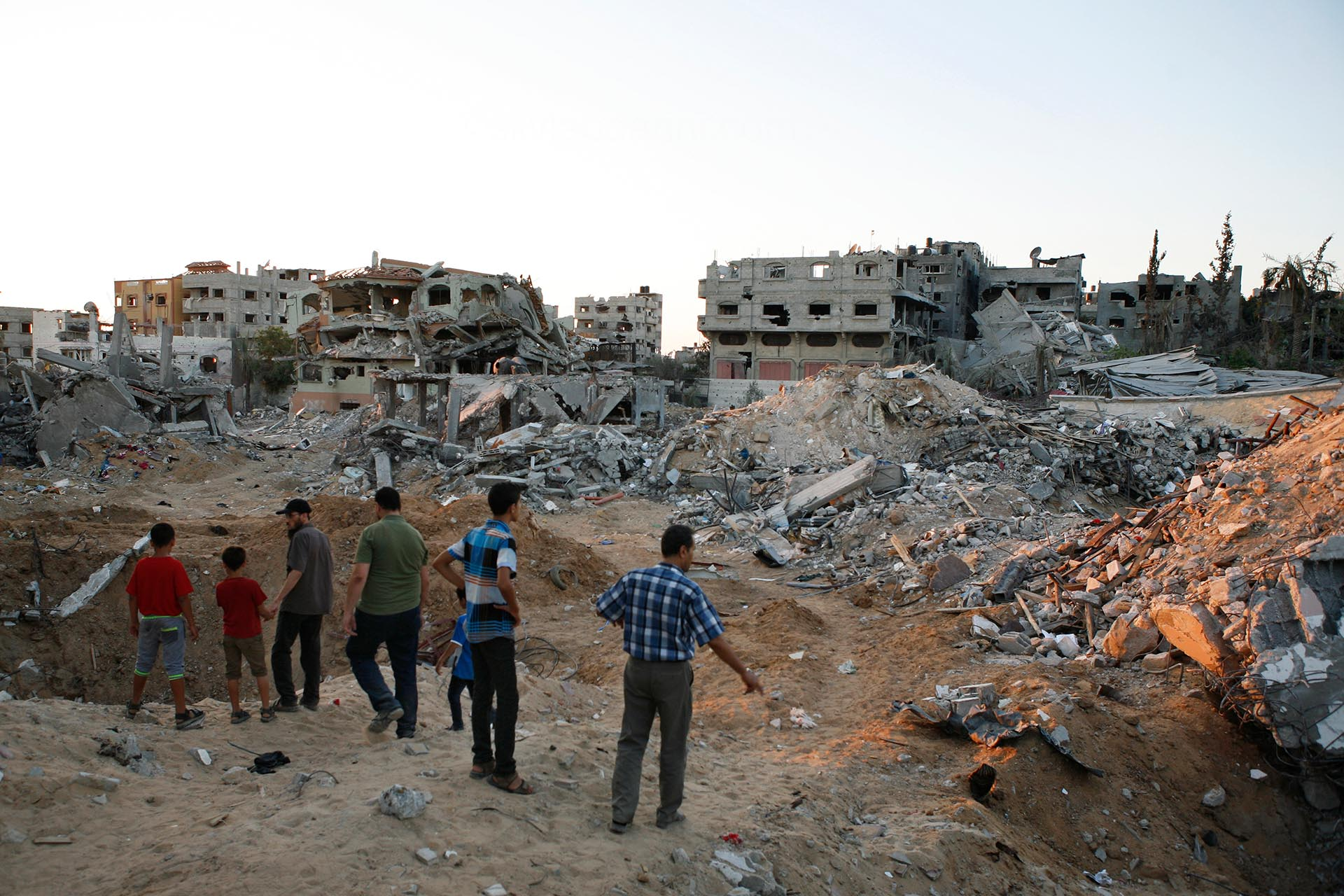 A group of men surveys the destruction in Shujayea, August 2014